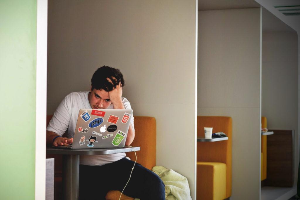 Mann starrt verzweifelt auf seinen Laptop